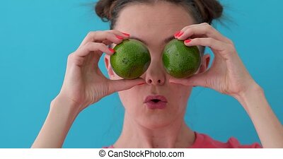 Young woman having fun with fruits - Young female grimacing...