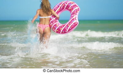 Young woman having fun with toy Inflatable ring donut on the...