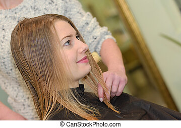 young woman having hair cut by stylist in salon