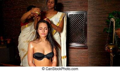 Young woman having head ayurveda treatment. Indian female masseuse in  ayurvedic spa salon.