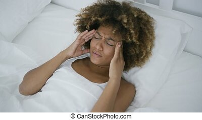 Young woman having headache lying in bed