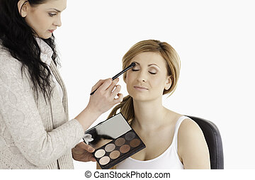 Young woman having her make up done by a make up artist