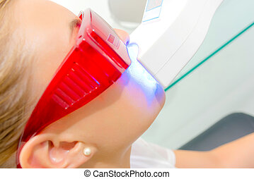 Young woman having her teeth laser whitened