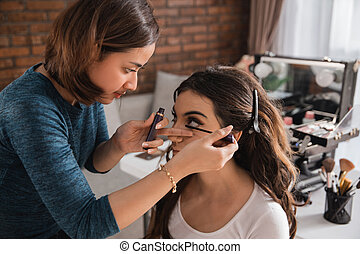 woman having make up applying by artist