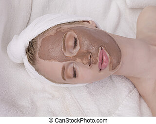 young woman having mud face mask
