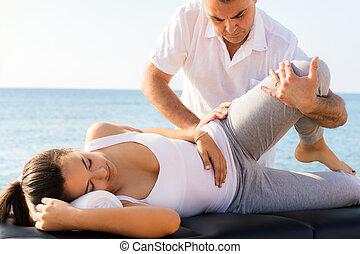 Young woman having osteopathic leg and femur treatment outdoors.