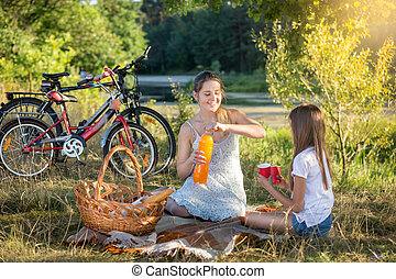 Young woman having picnic by the river with 10 years old...