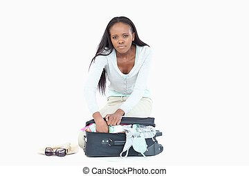 Young woman having problems packing her suitcase
