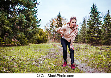 Young woman having rest after a run in autumn forest