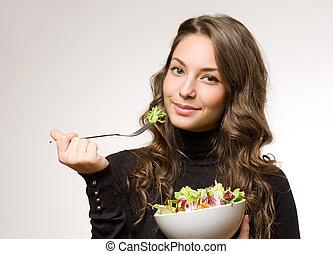 Young woman having salad.