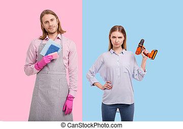 Young woman having screw gun while man holding sponges