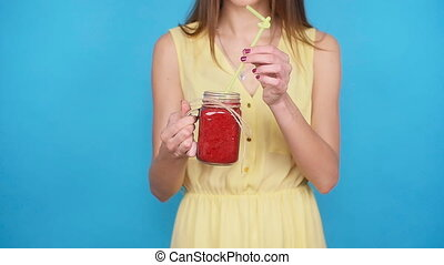 Young woman having smoothie drink made of super foods, fruits, nuts, berries