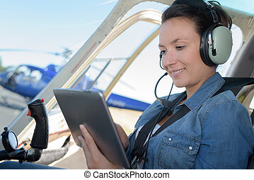 young woman helicopter pilot going through checklist before take off