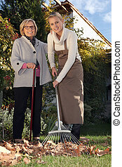 Young woman helping a senior with her garden