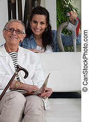 Young woman helping an elderly lady with her household chores