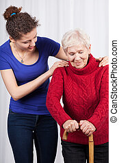 Young woman helping elderly lady
