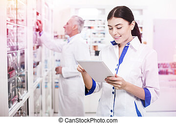 Young woman helping her colleague in a pharmacy