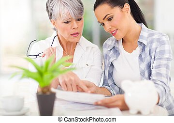 young woman helping her mother paying bills - beautiful...