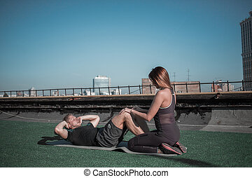 young woman helping man with situps.