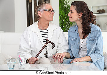 young woman helping senior lady at home