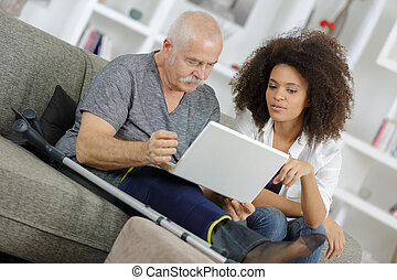 young woman helping senior man with a laptop computer