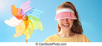 young woman hiding behind sun visor holding colorful ...