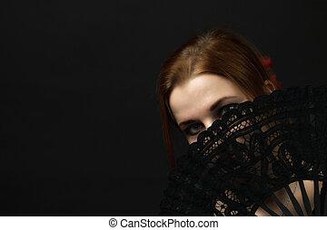 Young woman hiding face by a crochet black hand fan