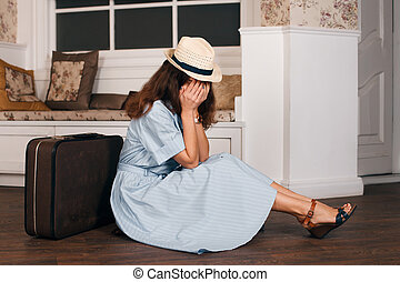 Young woman hiding her face in hands.