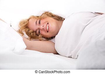 Young woman hiding in Bed under the sheets