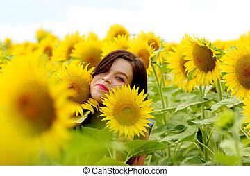 Young woman hiding in sunflowers