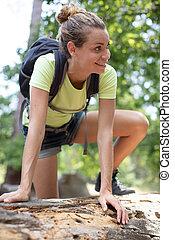 young woman hiker climbing rock on mountain peak cliff