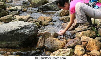 young woman hiker drink the stream water