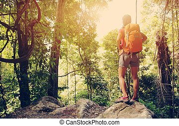 young woman hiker enjoy the view at tropical forest