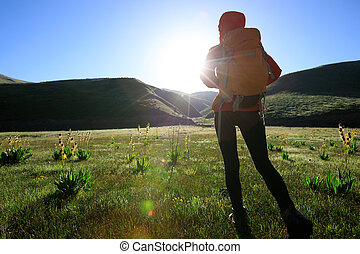 young woman hiker hiking in sunrise mountains