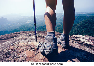 young woman hiker legs on mountain peak cliff edge