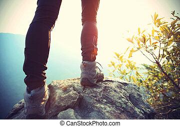 woman hiker legs on mountain peak rock