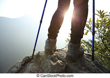 young woman hiker legs on mountain peak rock