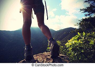 young woman hiker legs on sunrise mountain peak rock