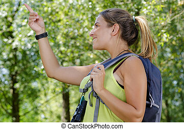 young woman hiker points on mountain peak