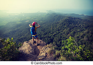Young woman hiker shouting on mountain peak cliff edge