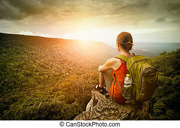 hiker sits on the edge of the cliff and enjoying sunrise
