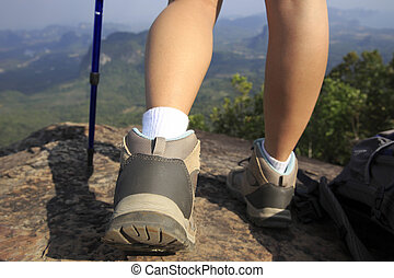 young woman hiker stand on cliff