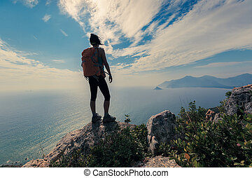 young woman hiker standing on mountain peak