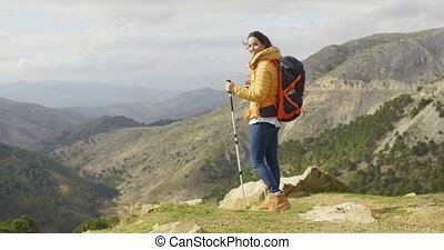 Young woman hiker standing overlooking a valley
