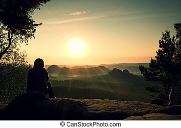 Young Woman hiker takes a rest bellow tree on peak of Mountain and enjoy autumn daybreak
