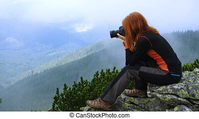 Young woman hiker taking a photo on the top of forested mountains