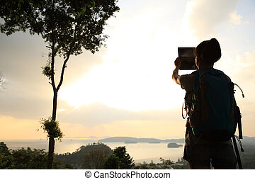 young woman hiker taking photo with digital tablet