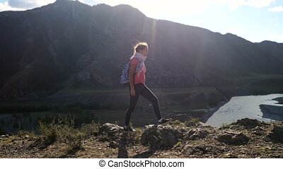 Young woman hiker taking photo with smart phone at mountain peak cliff with sun flare effects.