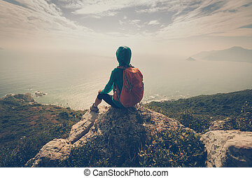 young woman hiker thinking on mountain peak