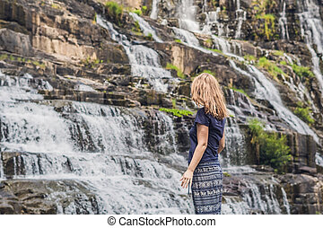 Young woman hiker, tourist on the background of Amazing Pongour Waterfall is famous and most beautiful of fall in Vietnam. Not far from Dalat city estimate 45 Km. Dalat, Vietnam
